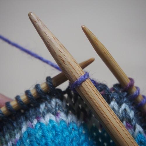 伏せ目と太い編み棒